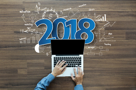 Foto de 2018 new year business success, Creative thinking drawing charts and graphs strategy plan ideas wooden table background, Inspiration concept with businessman working on laptop computer PC, Top View - Imagen libre de derechos