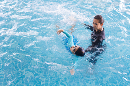 Foto de Girl learning to swim with coach at the leisure center - Imagen libre de derechos