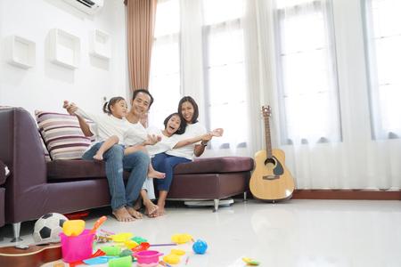 Foto de Happy asian family in living room at home, togetherness relaxation concept - Imagen libre de derechos