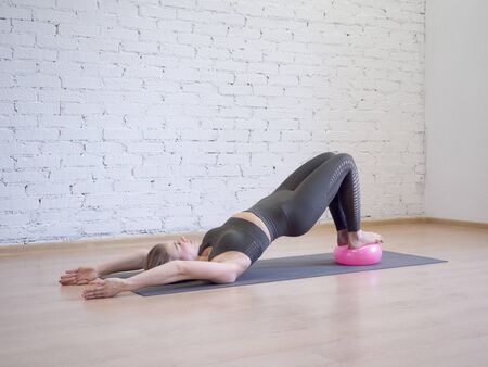 Photo pour Gluteal bridge on pink small fitness ball. Young caucasian woman doing pilates with special equipment in fitness studio. - image libre de droit