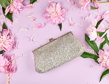 Photo for Closed silver women's handbag with sequins for cosmetics on a lilac background with blooming buds of pink peony, top view - Royalty Free Image