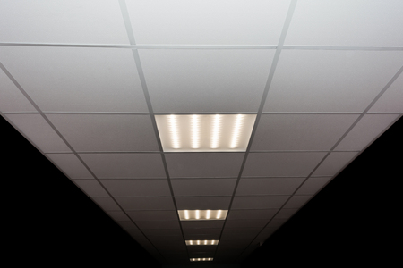 Foto de suspended ceiling of square porous plates and built-in LED lamp - Imagen libre de derechos
