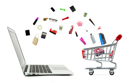 Foto de Shopping cart and laptop computer with products isolated on white background, shop online concept. - Imagen libre de derechos