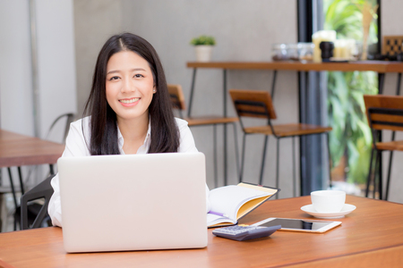 Photo for Beautiful asian young woman working online on laptop sitting at coffee shop, professional female freelancer using notebook computer with connect to internet for distance job. - Royalty Free Image