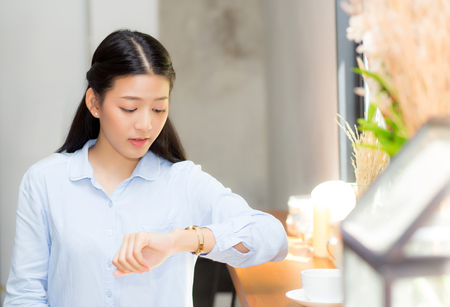 Foto de Beautiful asian young woman look at watch waiting for friend or someone, girl checking clock with appointment at coffee shop. - Imagen libre de derechos