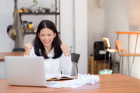 Photo pour Beautiful asian young woman working online on laptop sitting at coffee shop, professional female freelancer with paper crumpled and using notebook computer with connect to internet for distance job. - image libre de droit