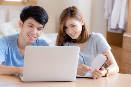 Foto de Beautiful young asian couple calculate expenses finance with laptop and planning together, woman writing notebook or note budget household, lifestyle family and business concept. - Imagen libre de derechos