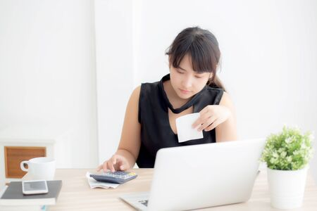 Foto de Beautiful young asian woman calculating expenses household and writing notebook on desk - Imagen libre de derechos