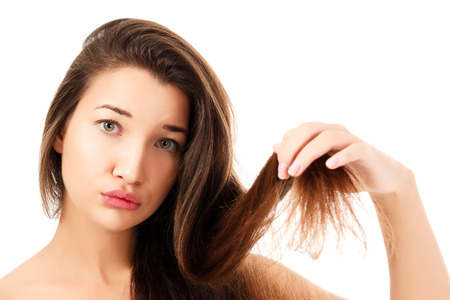 Foto de woman showing her fragile hair, white background, copyspace.  - Imagen libre de derechos