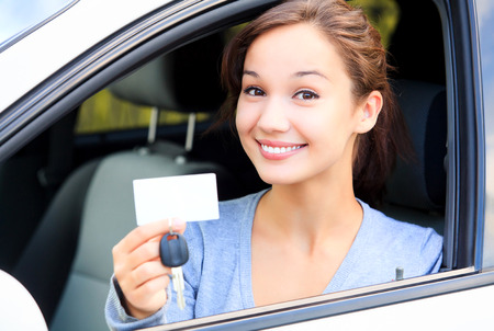 Photo pour Happy girl in a car showing a key and an empty white card for your message - image libre de droit
