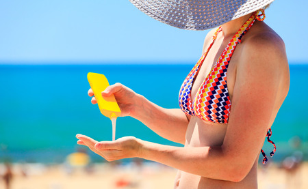 Foto de woman applying protective lotion before sunbathing at beach - Imagen libre de derechos