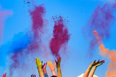 Photo for At the color Holi Festival, hands in the air, blue sky behind - Royalty Free Image