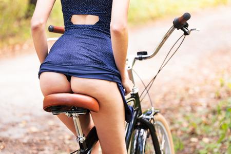 Foto de Young woman on a bike showing her beautiful ass, closeup shot - Imagen libre de derechos