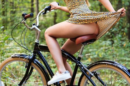Foto de Sexy young woman is riding on a bike in summer forest - Imagen libre de derechos