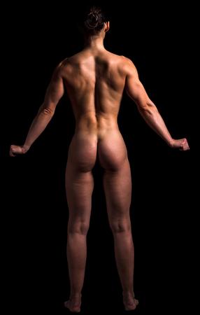 Photo pour Naked bodybuilder woman is posing against black background, isolated - image libre de droit