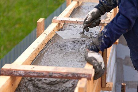 Photo pour Worker levels concrete in formwork using a trowel - image libre de droit