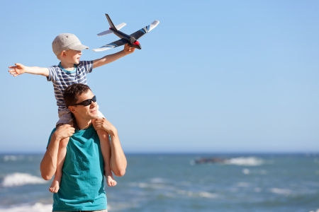 Foto de happy adorable boy holding toy plane and sitting on his young handsome father shoulders and having fun together outdoors - Imagen libre de derechos