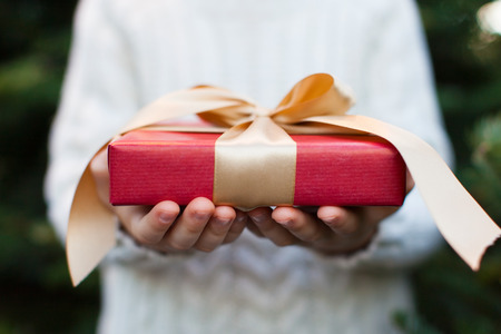Foto de close-up of nicely wrapped christmas gift being held by a child with no face visible, christmas tree in the background, christmas time concept - Imagen libre de derechos