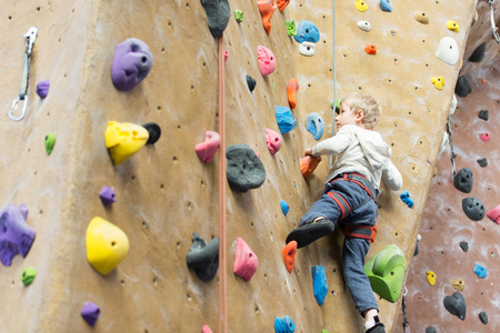 Photo pour little active boy rock climbing at indoor gym - image libre de droit