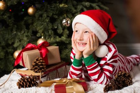Photo for portrait of beautiful smiling boy lying by christmas tree at home enjoying winter time at home waiting for a miracle to happen - Royalty Free Image