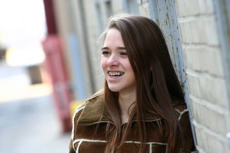 A teenage girl with braces leans against a wall in an urban alley and smiles