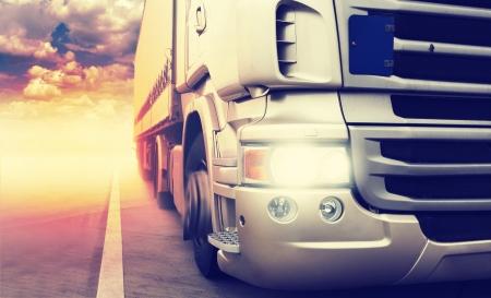 Cargo truck speeding on highway at sundown