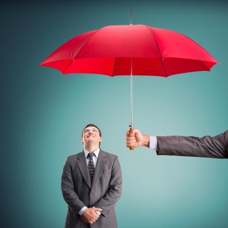 Cheerful businessman under an umbrella
