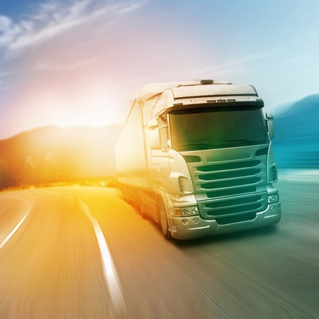 Photo pour Gray truck on highway road in sunlights - image libre de droit