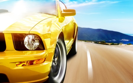 Yellow sport car on a narrow road