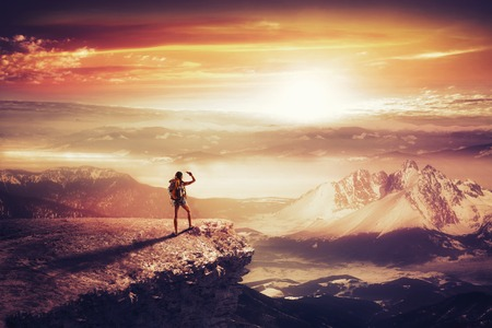 Pretty traveler woman with backpack on the top of mountain looking at sunset