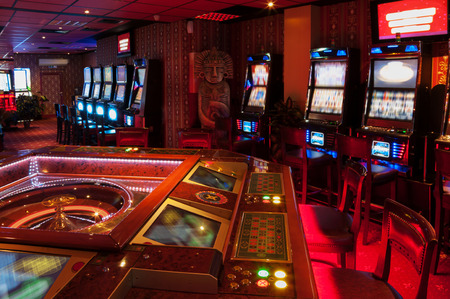 Foto de Roulette table and Slot machine. Red lighted casino. - Imagen libre de derechos