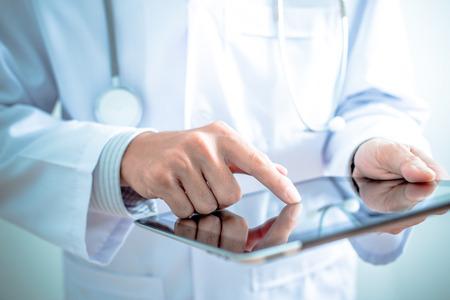Photo pour Doctor working on a digital tablet - image libre de droit