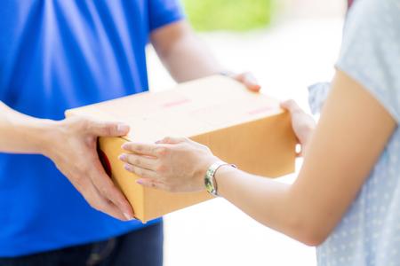 Foto de Asian woman receiving a package at home from a delivery guy - Imagen libre de derechos