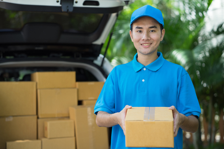 Foto de Asian Postman in blue uniform holding package. Delivery concept - Imagen libre de derechos