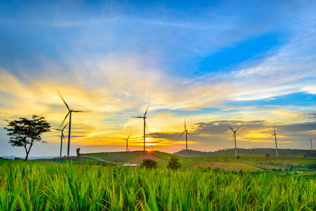 Foto de Wind generators turbines at sunset. Beautiful mountain landscape with wind generators turbines at Khao Kho mountain, Thailand. Renewable energy concept. - Imagen libre de derechos