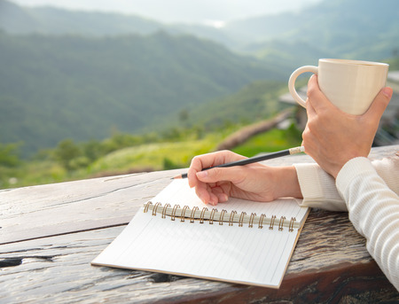 Photo pour A closeup of young woman holding a cup of coffee and taking a note with beautiful mountain view. A warm morning coffee and note book in woman hands with copy space. - image libre de droit