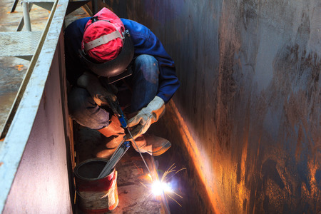Foto de Male  worker wearing protective clothing and repair welding industrial construction oil and gas or  storage tank inside confined spaces. - Imagen libre de derechos