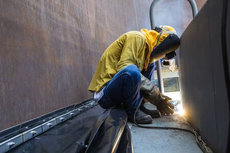 Foto de Male  worker wearing protective clothing and repair welding patition plate industrial construction oil and gas or  storage tank inside confined spaces. - Imagen libre de derechos