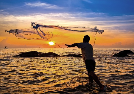 Foto de throwing fishing net during sunset , thai - Imagen libre de derechos
