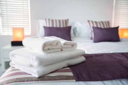 Photo pour Bath towels on the bed of hotel bedroom - image libre de droit