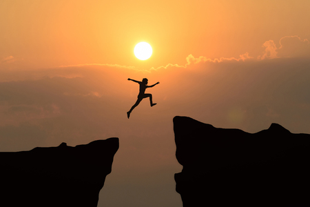 Foto de Man jump through the gap between hill.man jumping over cliff on sunset background,Business concept idea - Imagen libre de derechos