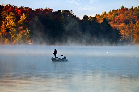 Silhouette of a man fishing in the morning fog with autumn colors on the trees.