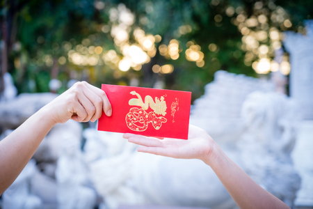 Photo for Close up hand holding red letter, sending and receiving red envelope Symbols of the Chinese New Year on golden bokeh background. gifts, festivals and celebration concept. - Royalty Free Image