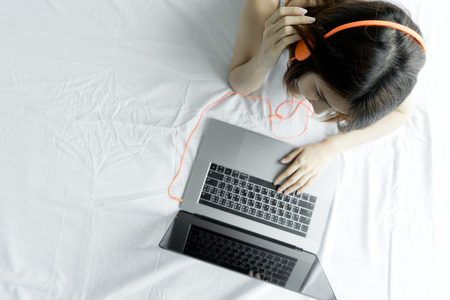 Photo for Woman typing laptop on white bed in morning. Young Asian girl using notebook computer listening music at home. Happy female use headphones watching movie on laptop with internet. people technology concept. - Royalty Free Image