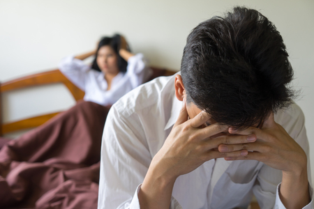 Foto de Young worried man on bed. Unhappy couple having problems in bedroom. Troubled wife and husband  worrying Serious and upset. family relationships conflict,  sexual life problems concept. - Imagen libre de derechos