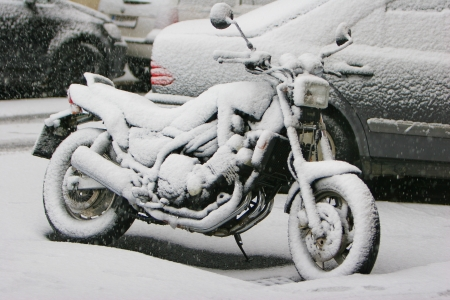 Motorcycle covered with snow at outdoor parking