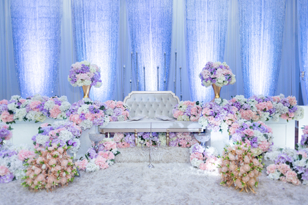 Foto de A raised stage in malay wedding where the bride and bridegroom sits in a traditional attire. it is usually decorated heavily with artificial flower. - Imagen libre de derechos