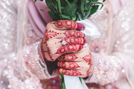 Photo pour Close up shot on happy bride holding hand bouquet showing big diamond ring before celebration. Hands decorated with henna. - image libre de droit