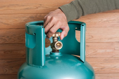 Photo for Closeup man's hand operating valve of LPG cylinder for cooking - Royalty Free Image