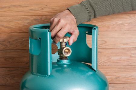 Photo pour Closeup man's hand operating valve of LPG cylinder for cooking - image libre de droit